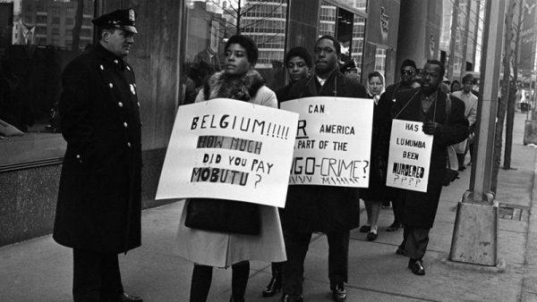 1961年2月11日、NYのベルギー領事館前で反ベルギー、ルムンバ支持のプラカードを掲げて抗議する人々 [AP Photo/Jacob Harris]